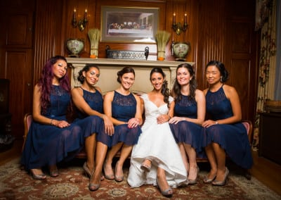 Here is a bridal party that coordinated their event with us at our seacoast nh hotel. The bride and bridal party are sitting on an aged red victorian couch. The bridesmaids are in blue dresses.
