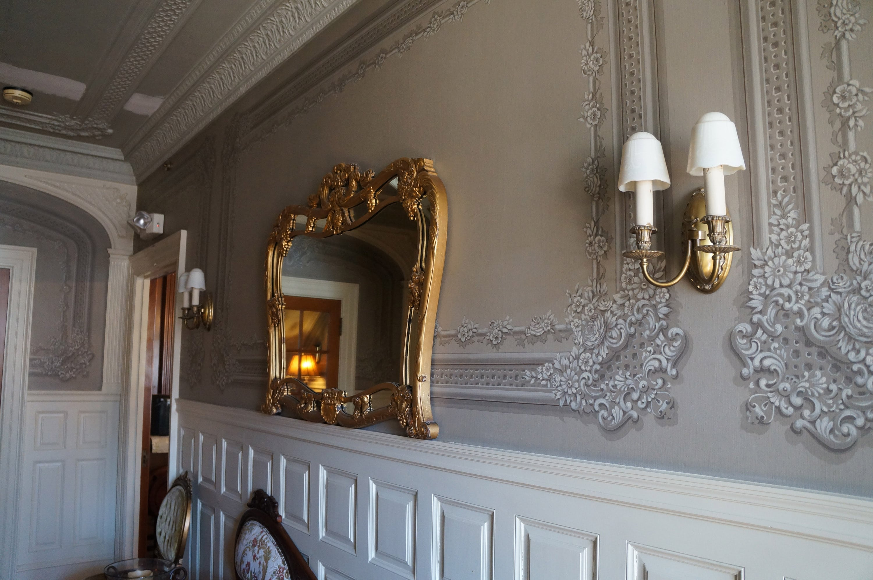 Here is a view of the beautiful victorian moldings on our wall in our durham nh hotel. There is a large gold mirror on the wall in between two golf wall lamps.