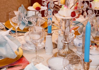 Here is a image of a tea room table dresssed with a three tier setting of deserts, place settings ready for guests and blue candles. Our tea room, unlike other durham NH area hotels, offers tea room experience.