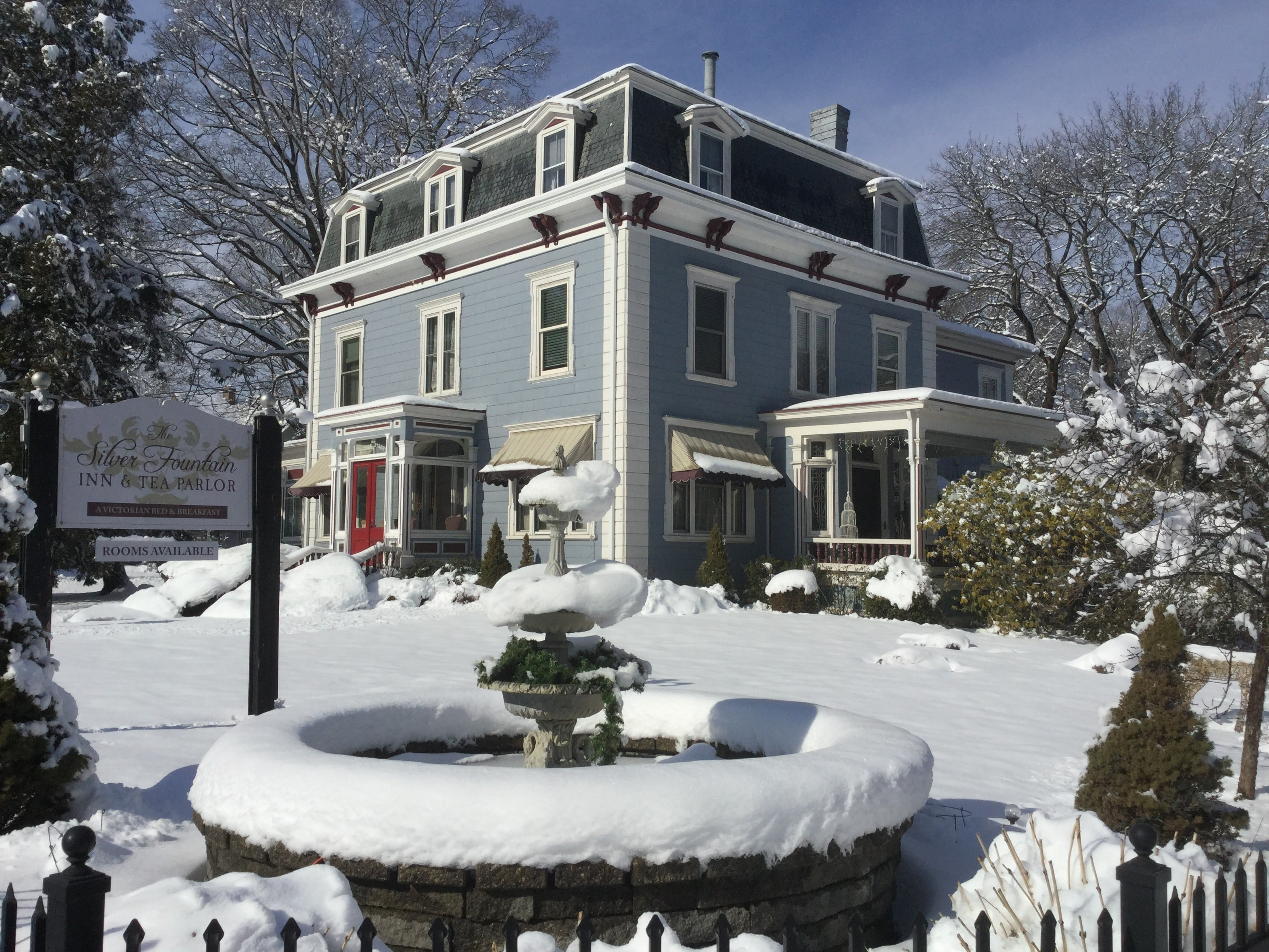Wintertime view of our hotel seacoast nh. This is from the side of the inn, showing a snow covered water fountain and the sign for Silver Fountain Inn & tea parlor.