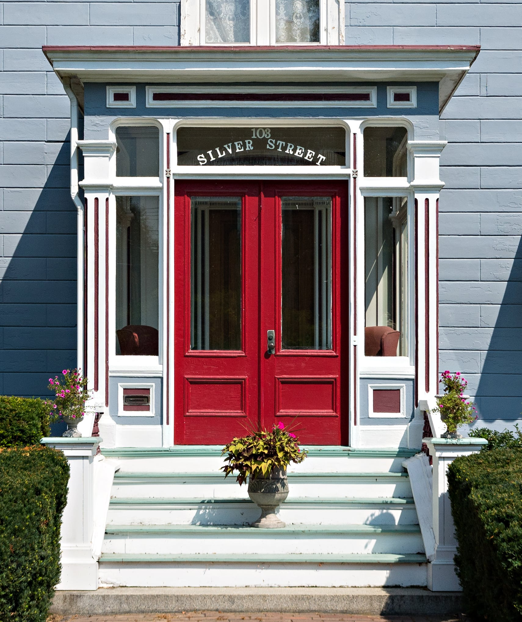 Here is the front door of the silver fountain inn. The door is large and red. There is a potted plant on the stairs of our hotel near dover nh and hedges lead up to the stairs.