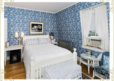 Check out this room at our Durham NH area hotel. This room is called the Eleanor. This is an image of the bed, wicker chairs, white tapestry, and blue victorian wall paper.