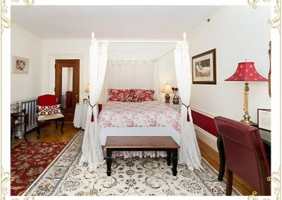 This is the Duchess, one of the room at one of the popular hotels in Dover NH. This image shows a bed and a writing desk. The walls are white with a red trim.